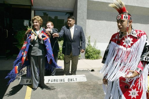 Laura Bush wears a traditional Native American wrap as she watches a musical performance before touring the Native American Community Health Center in Phoenix, Ariz., April 26, 2005. White House photo by Krisanne Johnson