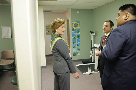 Dennis Huff, program director of the Native American Community Health Center, and Marcus Harrison, CEO of the Native American Community Health Center, give Laura Bush a tour of the Native American Community Health Center in Phoenix, Ariz., April 26, 2005.