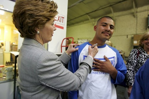 Laura Bush signs the shirt of a member of Homeboy Industries in Los Angeles April 27, 2005. Homeboy Industries is an job-training program that educates, trains and finds jobs for at-risk and gang-involved youth. White House photo by Krisanne Johnson