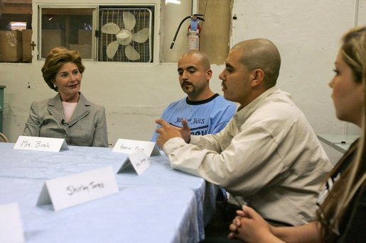 Laura Bush talks with, from left, Gabriel Flores, Archie Dominguez and Shirley Torres during a discussion at Homeboy Industries in Los Angeles April 27, 2005. Homeboys Industries is an job-training program that educates, trains and finds jobs for at-risk and gang-involved youth. White House photo by Krisanne Johnson