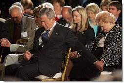 President George W. Bush and Laura Bush holds hands with guests while praying during a ceremony observing the National Day of Prayer in the East Room Thursday, May 5, 2005. White House photo by Krisanne Johnson