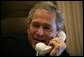 President George W. Bush smiles as he offers congratulations to Britain's Prime Minister Tony Blair during a phone call from Air Force One Friday, May 6 2005. White House photo by Eric Draper