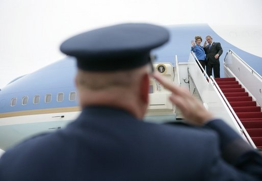 President George W. Bush returns a salute from Brigadier General David S. Gray, Commander, 89th Airlift Wing as he and Mrs Bush board Air Force One before departing Andrews Air Force Base for Latvia, Friday, May 6, 2005. White House photo by Eric Draper