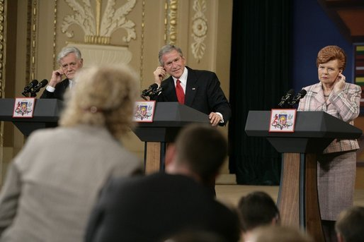 From left, Lithuanian President Valdas Adamkus, President George W. Bush and Latvia President Vaira Vike-Freiberga adjust their earphones to hear interpreters during a question and answer session Saturday, May 7, 2005, in Riga, Latvia. White House photo by Eric Draper