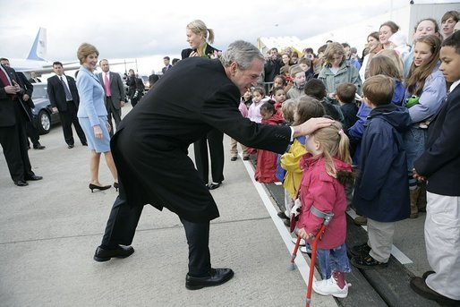 Greeted by flowers and smiles, President George W. Bush returns the gesture during his and Laura Bush's arrival in Maastricht, Netherlands, May 7, 2005. White House photo by Eric Draper