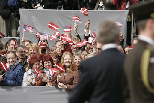 President George W. Bush turns to a crowd waving American and Latvian flags while visiting the Freedom Monument in Riga, May 7, 2005. White House photo by Paul Morse