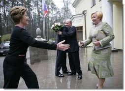President George W. Bush and Russia President Vladimir Putin embrace in the background as Mrs. Bush reaches out to Lyudmila Putina, Russia's first lady, as the Bushes arrived Sunday, May 8, 2005, at the Putin residence shortly after their arrival in Moscow.  White House photo by Eric Draper