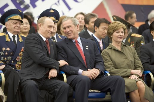 President George W. Bush and Russian President Vladimir Putin share a light moment as they sit with Laura Bush and other heads of state during a military parade marking the end of World War II in Moscow's Red Square, Monday, May 9, 2005. White House photo by Eric Draper