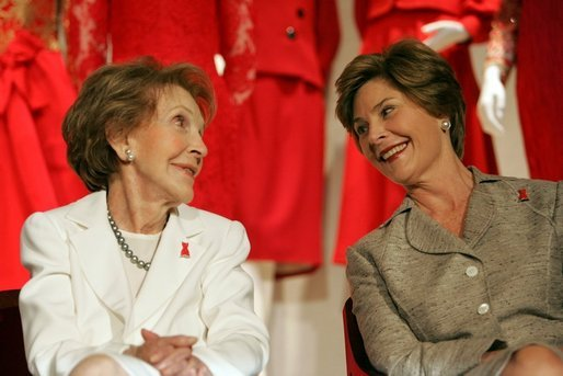 Laura Bush and former First Lady Nancy Reagan share a moment Thursday, May 12, 2005, at the John F. Kennedy Center for the Performing Arts during the unveiling of The Heart Truth's First Ladies Red Dress Collection. White House photo by Krisanne Johnson