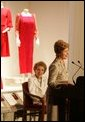 With former First Lady Nancy Reagan looking on, Laura Bush addresses the opening of The Heart Truth's First Ladies Red Dress Collection Thursday, May 12, 2005, at the John F. Kennedy Center for the Performing Arts in Washington D.C. Mrs. Bush, the ambassador for The Heart Truth, wore her red Carolina Herrera suit to the Bolshoi Theater in Moscow and to The Heart Truth's Red Dress Collection Fashion Show 2005 in New York City. White House photo by Krisanne Johnson