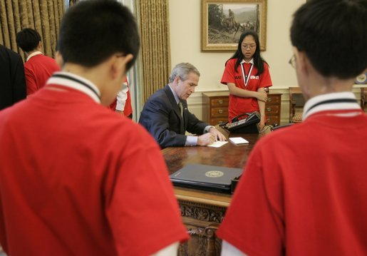 President George W. Bush signs notes to recipients of the 2005 MATHCOUNTS National Competition award during their visit to the Oval Office Thursday, May 12, 2005. White House photo by Paul Morse