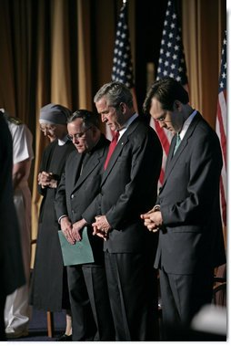President George W. Bush joins his hosts in prayer while attending the National Catholic Prayer Breakfast in Washington, D.C., Friday, May 20, 2005.  White House photo by Eric Draper