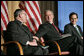 President George W. Bush reaches to Archbishop Charles J Chaput of Denver at the National Catholic Prayer Breakfast in Washington, D.C., Friday, May 20, 2005. Also pictured is Joseph Cella. White House photo by Eric Draper
