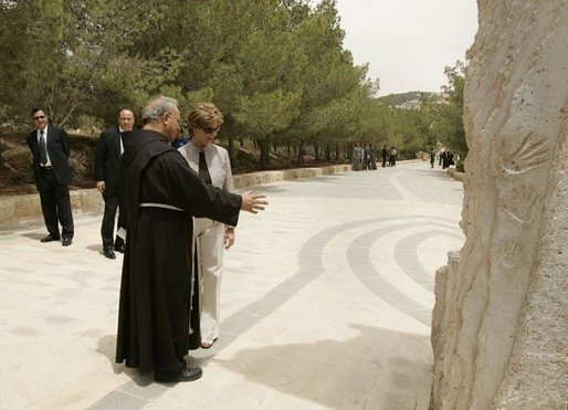Father Michele Piccirillo, head of the Franciscan Archeology Society, discusses a monument with Laura Bush during her tour of Mount Nebo in Jordan Saturday, May 21, 2005. White House photo by Krisanne Johnson