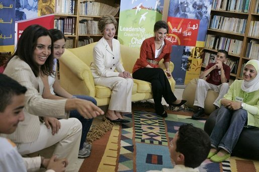 Soraya Sulti, regional director of INJAZ, left, and students at the Discovery School of Swaifiyeh Secondary School in Amman, Jordan, share their experiences with INJAZ with Laura Bush and Queen Raina, center right, May 22, 2005. INJAZ promotes entrepreneurship and community leadership among Jordan's youth by teaching entrepreneurship, business ethics, leadership and community involvement. White House photo by Krisanne Johnson