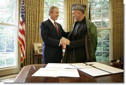 President George W. Bush and President Hamid Karzai of Afghanistan, shake hands Monday, May 23, 2005, in the Oval Office of the White House after signing a joint declaration that commits both the United States and Afghanistan to closely work together to enhance Afghanistan's long-term democracy, prosperity and security.  White House photo by Eric Draper