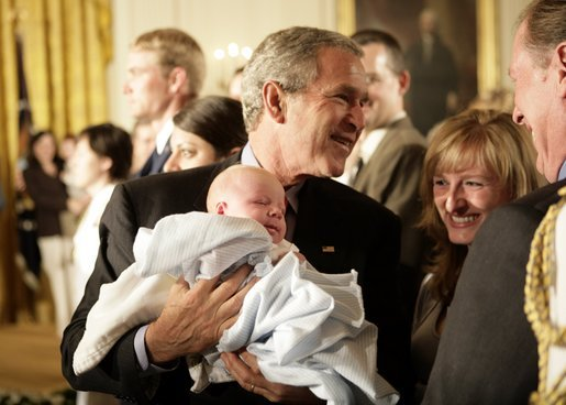 President George W. Bush holds one-month-old Trey Jones as he greets the audience Tuesday, May 24, 2005, after remarks on bioethics in the East Room of the White House. White House photo by Eric Draper