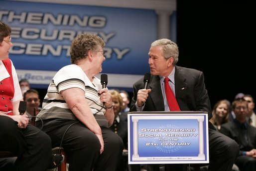 President George W. Bush talks with a fellow stage participant during a conversation about strengthening Social Security at Greece Athena Middle and High School in Greece, N.Y., Tuesday, May 24, 2005. White House photo by Paul Morse