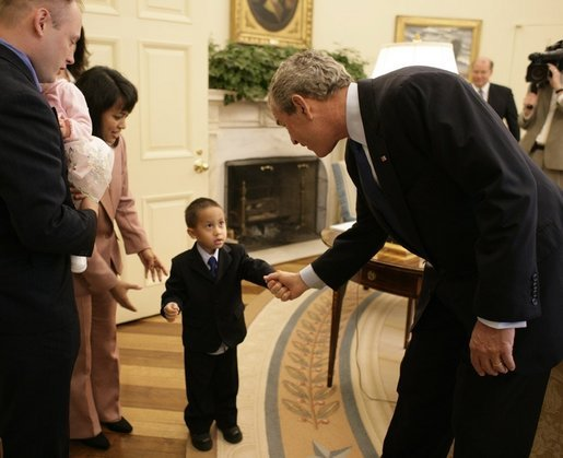 President George W. Bush reaches out for the hand of young Chandra Fincke, son of Lt. Colonel Mike Fincke and wife Renita, as the family joined fellow crewmembers of International Space Station flights for a visit to the Oval Office. White House photo by Eric Draper