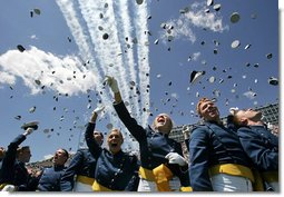 Graduates toss their hats into the air as the contrails from five F-16's stream overhead during the U.S. Air Force Academy graduation in Colorado on Wednesday, June 1, 2005. Nine-hundred and six graduates became commissioned officers in the U.S. Air Force after their four-year curriculum that began shortly before Sept. 11, 2001.  White House photo by David Bohrer