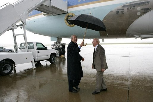 President George W. Bush shares an umbrella and a laugh Thursday, June 2, 2005, at Fort Campbell, Ky., with Freedom Corps greeter Dr. John Cotthoff, an 81-year-old volunteer physician at the St. Luke Free Clinic in nearby Hopkinsville. White House photo by Eric Draper