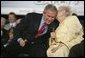 President George W. Bush leans in for a whisper from Cecil Ferrell, founder and owner of Ferrell's Hamburgers in Hopkinsville, Ky., one of the participants in the President's Conversation on Strengthening Social Security Thursday, June 2, 2005, at the Hopkinsville Christian County Conference and Convention Center. White House photo by Eric Draper