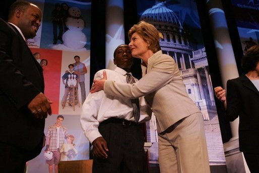 "Laura Bush attends the Opening Session of the 2005 National Big Brothers Big Sisters Conference, June 9, 2005, at the Marriott Wardman Park Hotel. Washington, D.C. On-stage participants include: Vincent ""Vinny"" Thomas, Big Brother, left, ; and Parry Elliott, Little Brother, 13-years-old, being embraced by Mrs. Bush. White House photo by Krisanne Johnson"