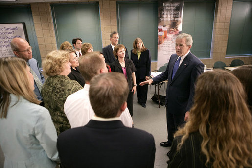 President George W. Bush talks with training volunteers for Medicare enrollment during a visit Friday, June 17, 2005, to a training session at the Maple Grove Community Center in Maple Grove, Minn. White House photo by Eric Draper