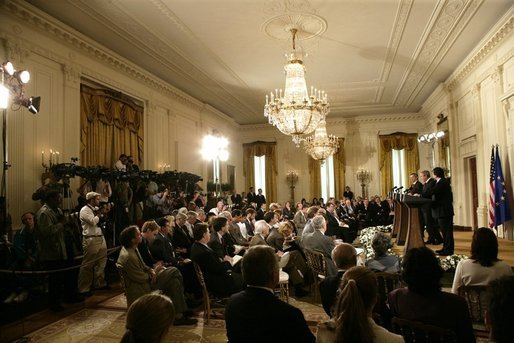 The media crowds into the East Room of the White House Monday, June 20, 2005, as President George W. Bush, European Union President Jean-Claude Juncker, left, and European Commission President Jose Manuel Barroso hold a joint press conference. White House photo by Eric Draper