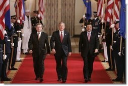 President George W. Bush leads European Union President Jean-Claude Juncker, left, and European Commission President Jose Manuel Barroso as they head to a joint press availability in the East Room Monday, June 20, 2005.  White House photo by Paul Morse