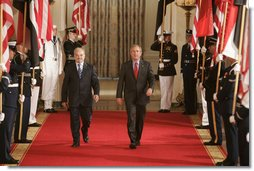 President George W. Bush walks with Dr. Ibrahim Jaafari, Prime Minister of Iraq, toward the East Room Friday, June 24, 2005, to meet the media.  White House photo by Paul Morse