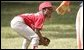 Taylor Paige Nevils of South Side Little League Memphis Red Sox from Chicago, peers up at Dugout, the Little League mascot, during a T-ball game on the South Lawn Sunday, June 26, 2005. White House photo by Paul Morse