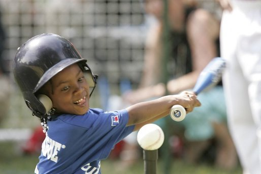 "Shaquana Smith of the Jackie Robinson South Ward Little League Black Yankees of Newark, N.J., swings at the ball Sunday, June 26, 2005, during ""Tee Ball on the South Lawn."" White House photo by Paul Morse"