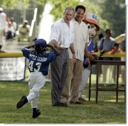 "Shaquana Smith holds onto her hat as she runs to President George W. Bush and White House Tee Ball Commissioner Barry Larkin after her Memphis Red Sox played the Black Yankees of Newark during Sunday's ""Tee Ball on the South Lawn.""  White House photo by Paul Morse"