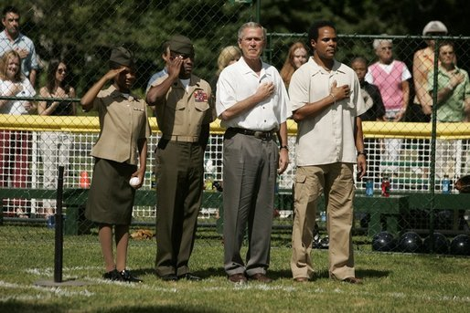 "President George W. Bush is joined by Barry Larkin, White House Tee Ball Commissioner of the Game and Young Marines as they stand for the National Anthem Sunday, June 26, 2005, during ""Tee Ball on the South Lawn."" White House photo by Krisanne Johnson"