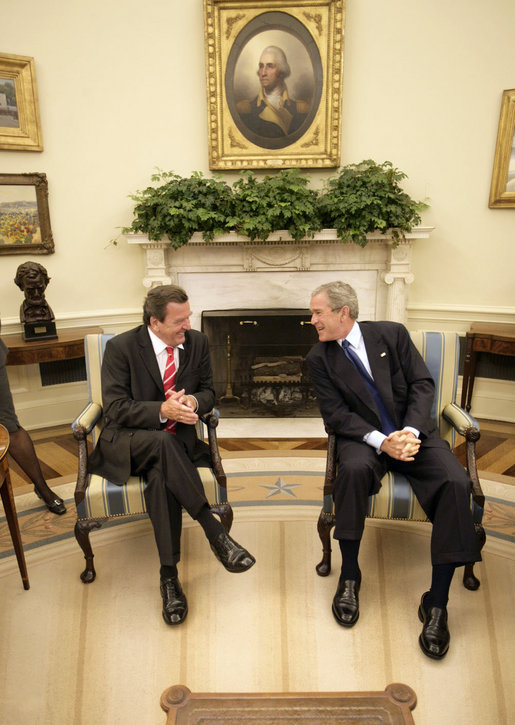 President George W. Bush and German Chancellor Gerhard Schroeder talk just before meeting with the press in the Oval Office Monday, June 27, 2005. White House photo by Eric Draper