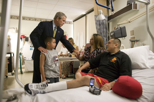 President George W. Bush holds the hand of Elvira Flores, wife of Lance Cpl. Alberto Flores, as their son A.J., watches during the President's visit Friday, July 1, 2005, to Walter Reed Army Medical Center. Lance Cpl. Flores, from Salinas, Calif., is being treated for injuries received while serving in Operation Iraqi Freedom. White House photo by Eric Draper