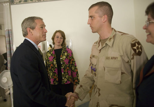President George W. Bush shakes the hand of Capt. Daniel Gade, a double Purple Heart recipient, during the President's visit Friday, July 1, 2005, to Walter Reed Army Medical Center. The Minot, North Dakota soldier is recovering from injuries sustained during Operation Iraqi Freedom. In the background is his wife, Wendy. White House photo by Eric Draper
