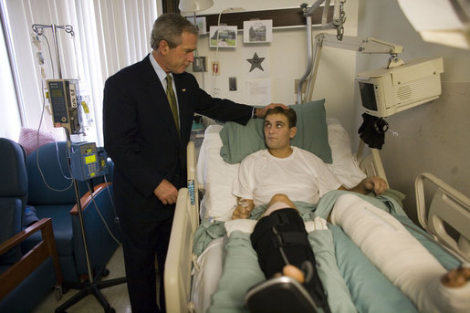 President George W. Bush spends a moment with Cpl. Cole Hansen of Canby, Minn., during a visit to Walter Reed Army Medical Center Friday, July 1, 2005. Cpl. Hansen is recovering from wounds received while serving in Operation Iraqi Freedom. White House photo by Eric Draper