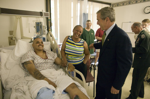 President George W. Bush shares a light moment with Sgt. John Iverson and his wife, Pamela, during the President's visit Friday, July 1, 2005, to Walter Reed Army Medical Center. The Long Beach, California soldier is recovering from injuries sustained while serving in Operation Iraqi Freedom. White House photo by Eric Draper