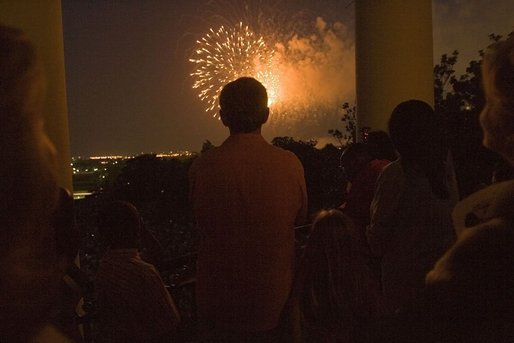 President George W. Bush watches Fourth of July fireworks from the balcony of the White House Monday evening. The Independence Day celebration was preceded by a birthday fete for the President, who will turn 59 on July 6. White House photo by Krisanne Johnson