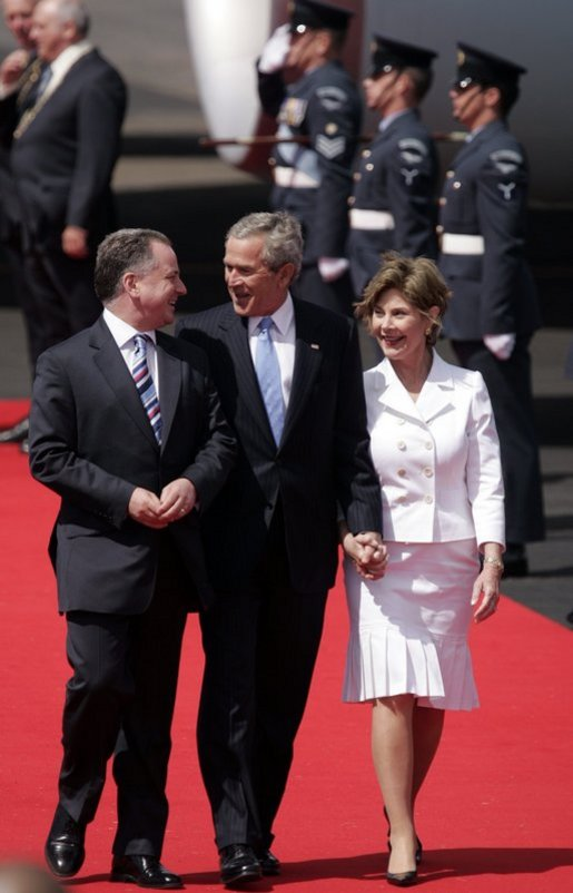 President George W. Bush and Laura Bush walk with Scotland's First Minister Jack McConnell during the playing of national anthems upon their arrival at Glasgow's Prestiwick Airport, July 6, 2005. White House photo by Paul Morse