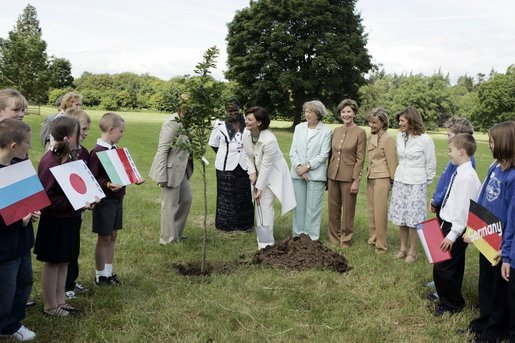 Mrs. Laura Bush looks on as Cherie Blair, wife of Prime Minister Tony Blair, takes the first dig during a tree-planting ceremony Thursday, July 1, 2005, at Glamis Castle, Scotland. White House photo by Krisanne Johnson