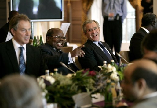 President George W. Bush shares a light moment with Tanzanian President Benjamin Mkapa during the morning session of the G8 Summit Friday, July 8, 2005, at Gleneagles Hotel in Auchterarder, Scotland. Britain's Prime Minister Tony Blair, who returned from London late last night, sits at left. White House photo by Eric Draper