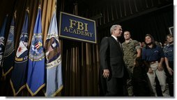 President George W. Bush walks on stage Monday, July 11, 2005, at the FBI Academy in Quantico, Va., where he spoke on the ongoing accomplishments and efforts in the war on terror.  White House photo by Eric Draper