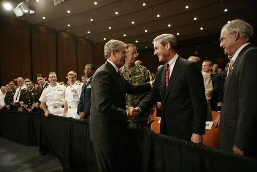 President George W. Bush shakes hands Monday, July 11, 2005, with Robert Mueller, Director of the Federal Bureau of Investigation as Porter Goss, right, Director of the Central Intelligence Agency, looks on. The President had just finished speaking on the war on terrorism at the FBI Academy in Quantico, Va. White House photo by Eric Draper