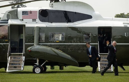 President George W. Bush waves as he and staff members arrive on the South Lawn Monday, July 11, 2005. White House photo by Lynden Steele