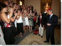 President Bush is applauded by members of the University of Georgia women's swimming and diving team, as he prepares put on the team hat Tuesday, July 12, 2005 at The White House, as part of ceremonies honoring the 2004 and 2005 NCAA Sport Championship teams.  White House photo by Eric Draper