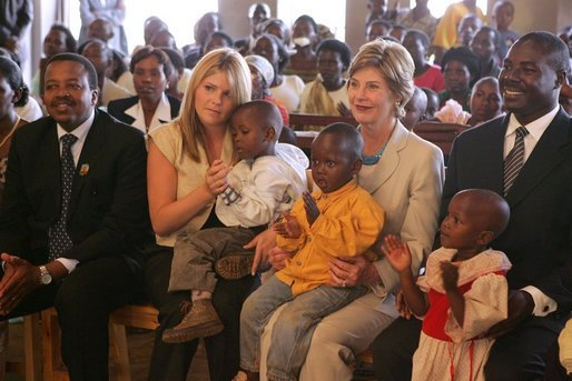 Laura Bush and daughter Jenna sit with children as they visit the Kagarama Church, Thursday, July 14, 2005, in Kigali, Rwanda. White House photo by Krisanne Johnson