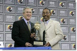 President George W. Bush receives the Black Expo Lifetime Achievement Award by Black Expo Chairman Arvis Dawson during the Indiana Black Expo Corporate Luncheon in Indianapolis, Indiana, Thursday, July 14, 2005.  White House photo by Eric Draper